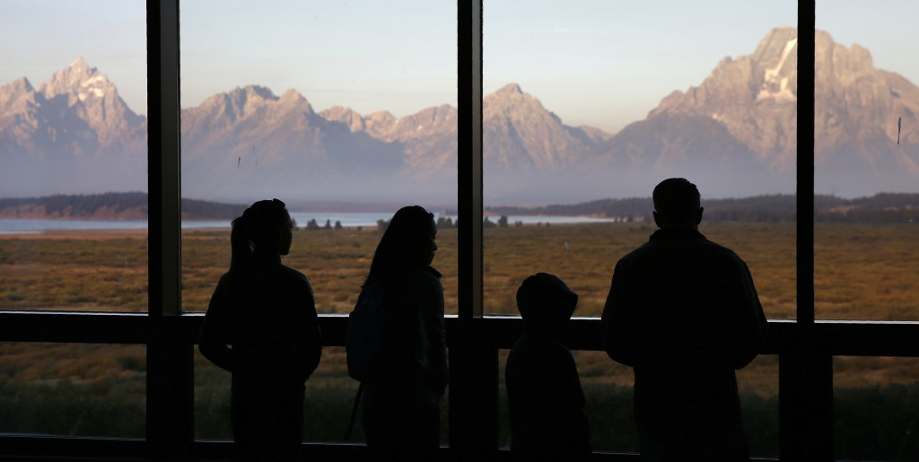 FILE - In this Aug. 28, 2016 file photo visitors watch the morning sun illuminate the Grand Tetons from within the Great Room at the Jackson Lake Lodg...