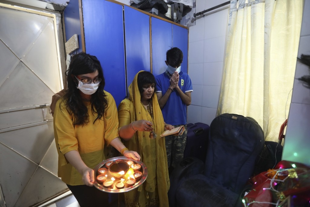 A family, wearing face masks as a precaution from coronavirus, prays inside their house on the first day of Navratri festival, where Hindu fast for ni...