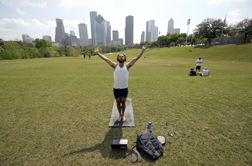 Trey Evans participates in an online yoga class using his laptop and headphones outside at Eleanor Tinsley Park near downtown Houston, Tuesday, March ...
