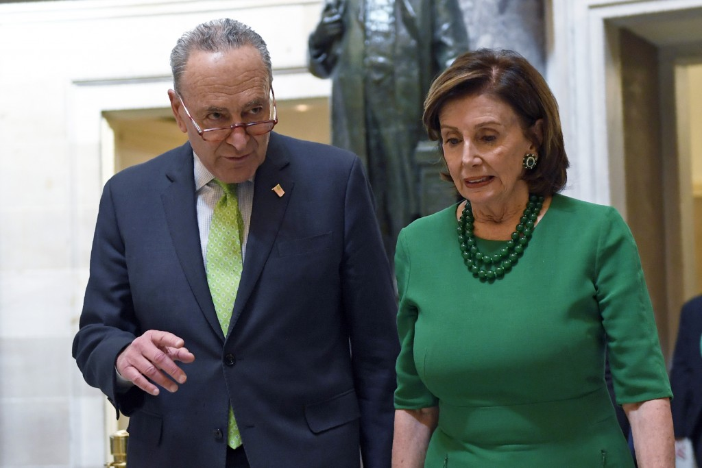 FILE - In this March 12, 2020, file photo Senate Minority Leader Sen. Chuck Schumer of N.Y., and House Speaker Nancy Pelosi of Calif., walks together ...