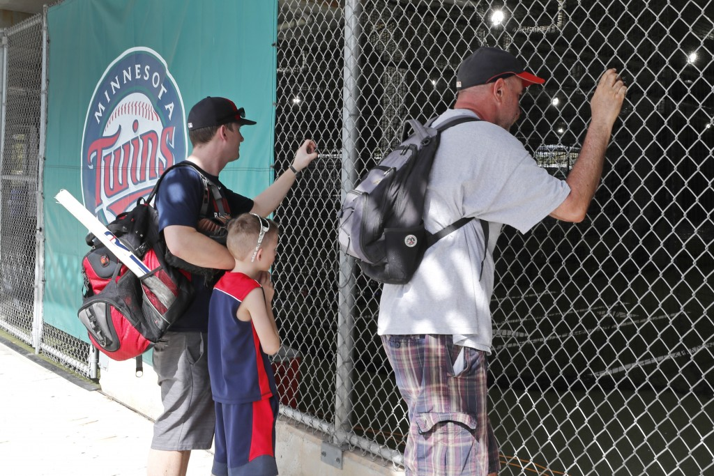 FILE - In this March 12, 2020, file photo, baseball fans look through a fence at Hammond Stadium after a game between the Minnesota Twins and the Balt...