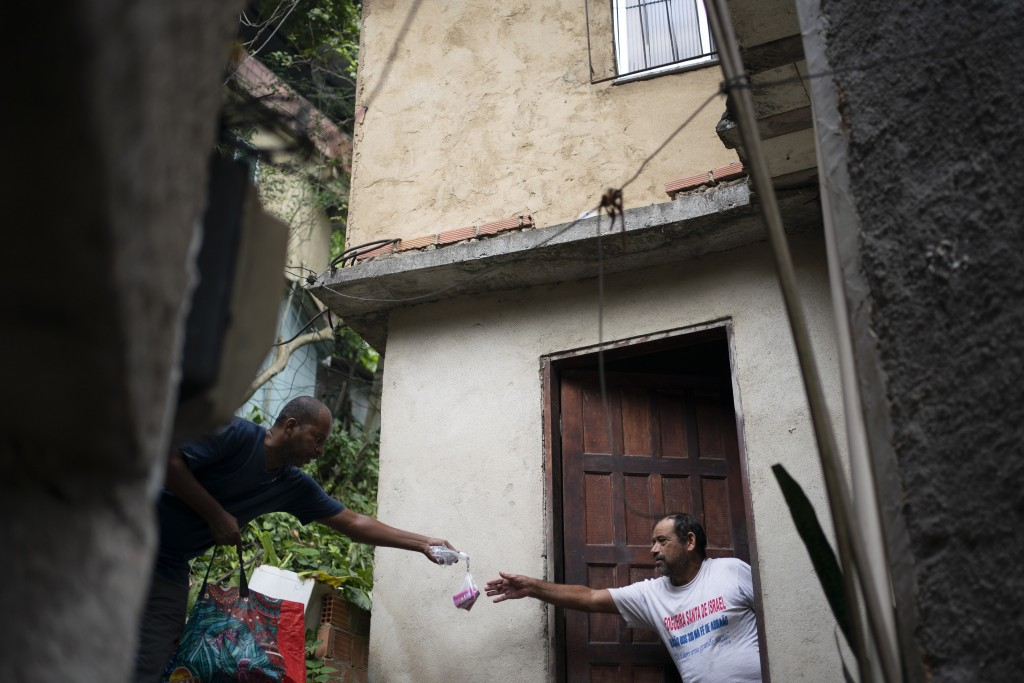 A local volunteer hands soap to a resident in an effort to avoid the spread of the new coronavirus in the Rocinha slum of Rio de Janeiro, Brazil, Tues...