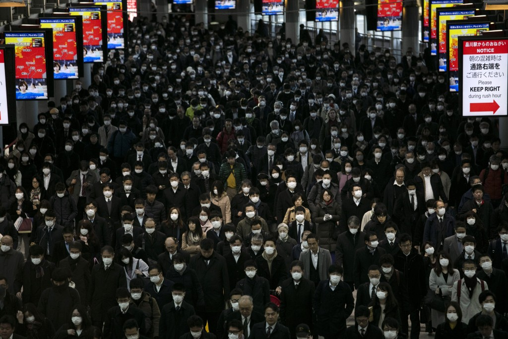 FILE - In this Tuesday, March 3, 2020, file photo, a large crowd wearing masks commutes through Shinagawa Station in Tokyo. World War II references ar...