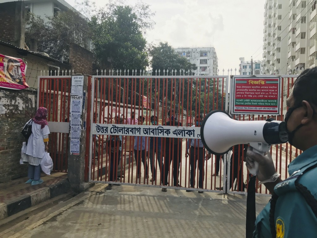In this Monday, March 23, 3030 photo, a policeman urges residents not to come out of their homes as residents stand behind a gate, hours after the sec...