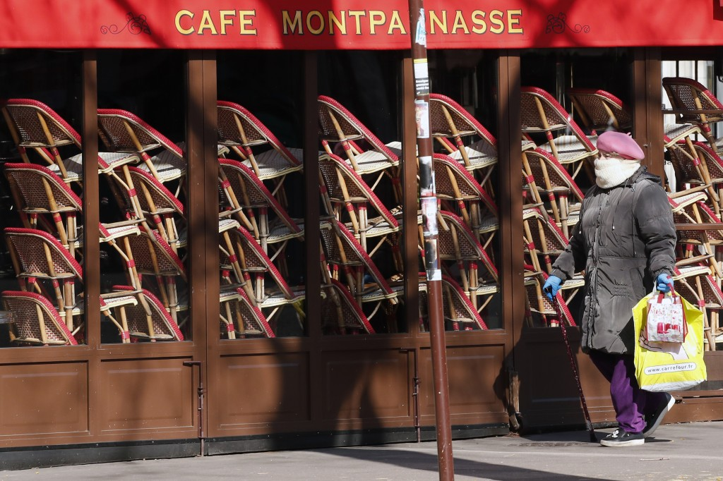 A woman walks by a closed restaurant in Paris, Tuesday, March 24, 2020. French President Emmanuel Macron urged employees to keep working in supermarke...
