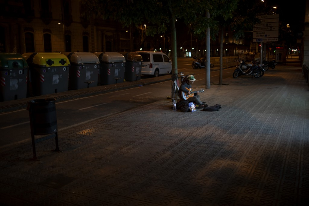 In this Saturday, March 21, 2020 photo, Kevin, 32, from France, plays guitar in front of a supermarket in Barcelona, Spain. Kevin, who has slept on th...