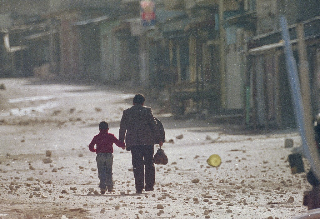 FILE - In this Dec. 11, 1987 file photo, a man holds his son's hand as they make their way along a debris littered street in the Balata refugee camp n...