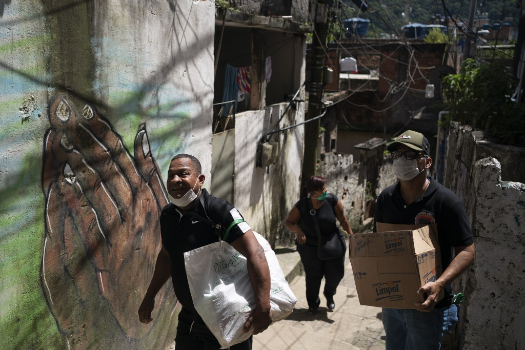 Volunteers carry packages with soap and detergent to be distributed in an effort to avoid the spread of the new coronavirus in the Rocinha slum in Rio...