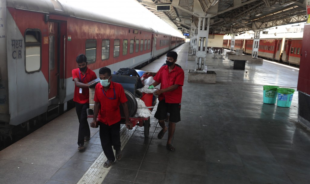 FILE - In this Monday, March 23, 2020, file photo, railway workers wearing masks push a handcart at Lokmanya Tilak Terminus in Mumbai, India. India's ...