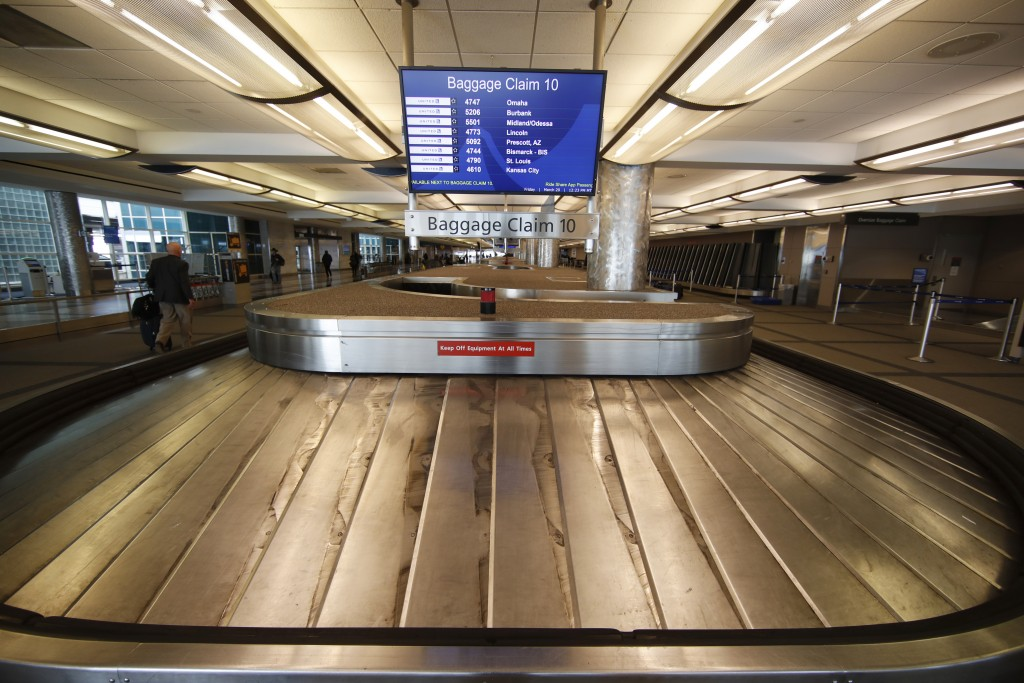 FILE - In this March 20, 2020 file photo, an empty baggage carousel spins in Denver International Airport as travelers deal with the spread of the cor...