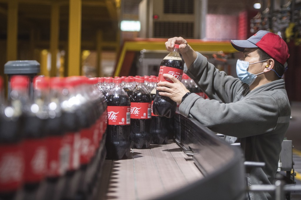 This Tuesday, March 24, 2020, photo released by China's Xinhua News Agency, shows a worker wearing a face mask on a production line at a Swire Coca-Co...