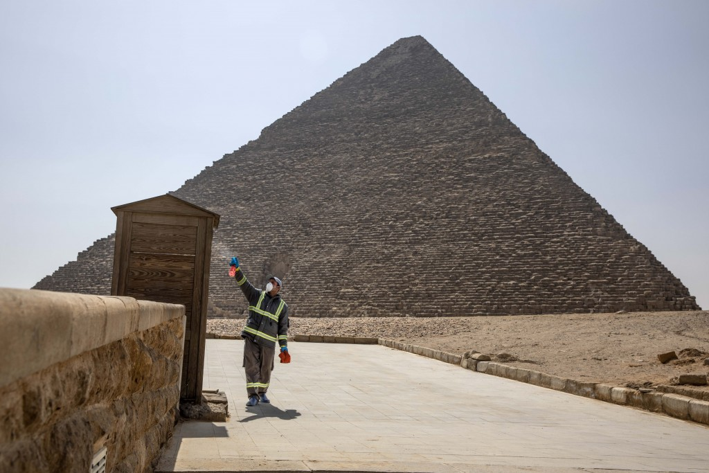 Municipal workers sanitize the areas surrounding the Giza pyramids complex in hopes of curbing the coronavirus outbreak in Egypt, Wednesday, March 25,...