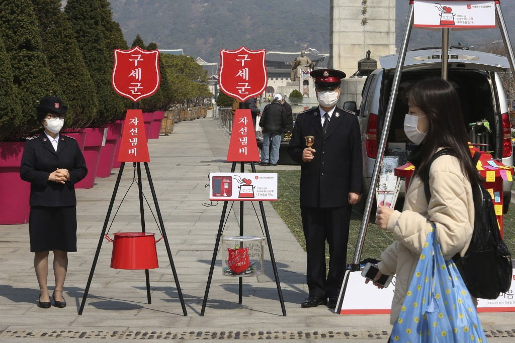 Members of the Salvation Army stand with charity pots during a campaign for the donation of face masks and money to impoverished people amid the sprea...
