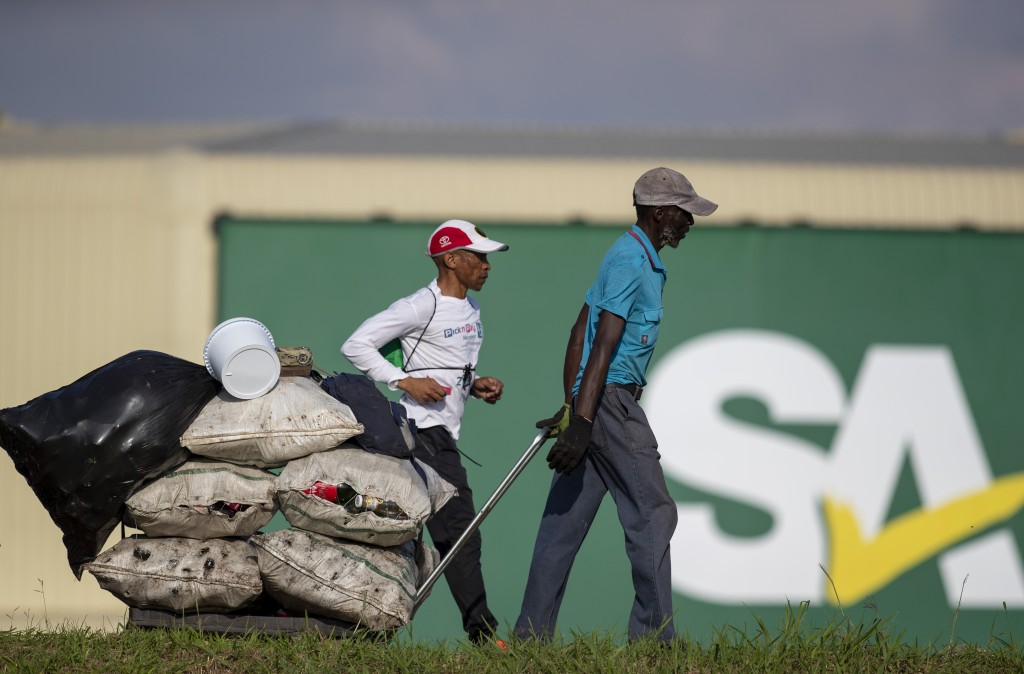 A man pulling a trolley loaded with recycling material walks in the industrial area in Daveyton, east of Johannesburg, South Africa, Tuesday, March 24...