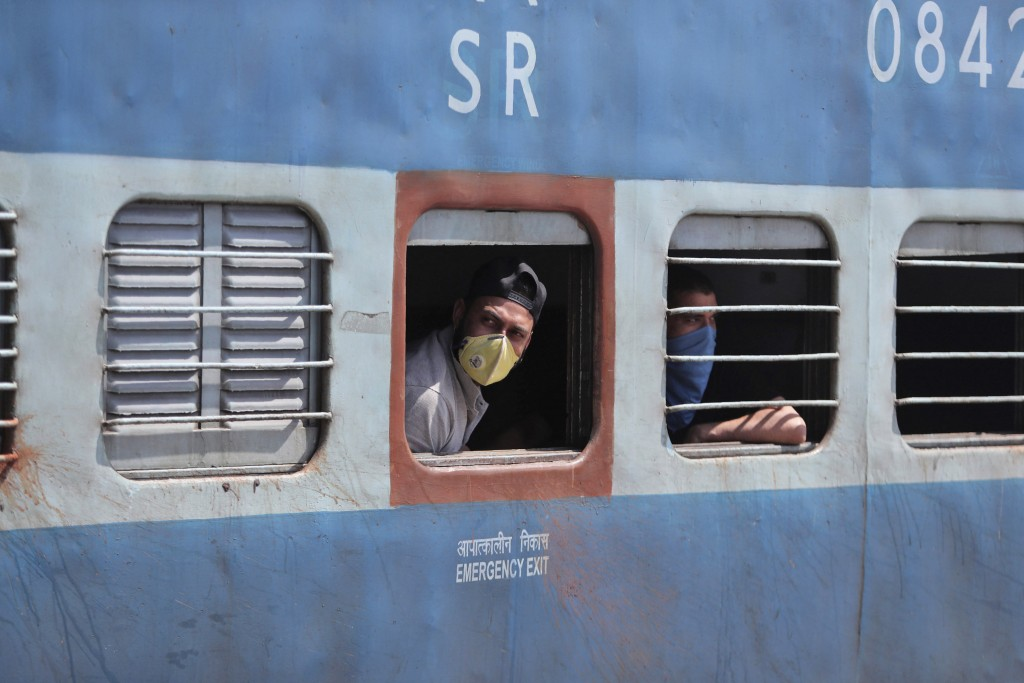 FILE - In this Monday, March 23, 2020, file photo, passengers wearing masks look out from a train in Jammu, India. India's colossal passenger railway ...