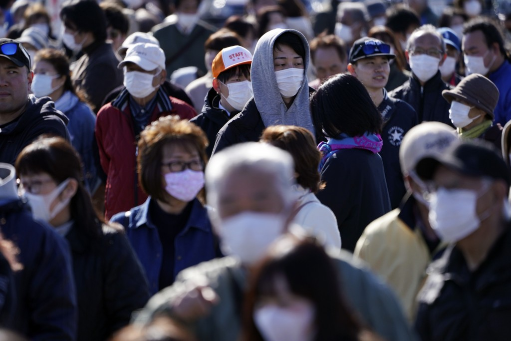 Spectators wait to see the Olympic flame display ceremony in Iwaki, Fukushima Prefecture, northern Japan, Wednesday, March 25, 2020. IOC President Tho...