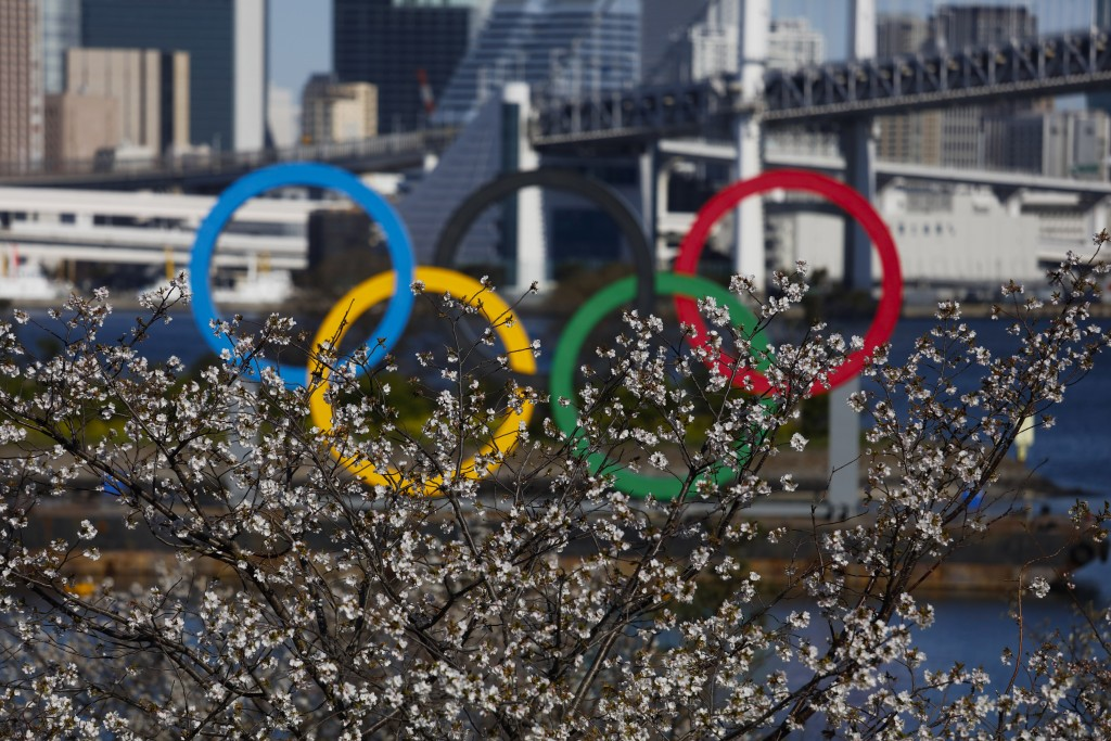 The Olympic rings are seen behind cherry blossoms Wednesday, March 25, 2020, in the Odaiba section of Tokyo. Not even the Summer Olympics could withst...