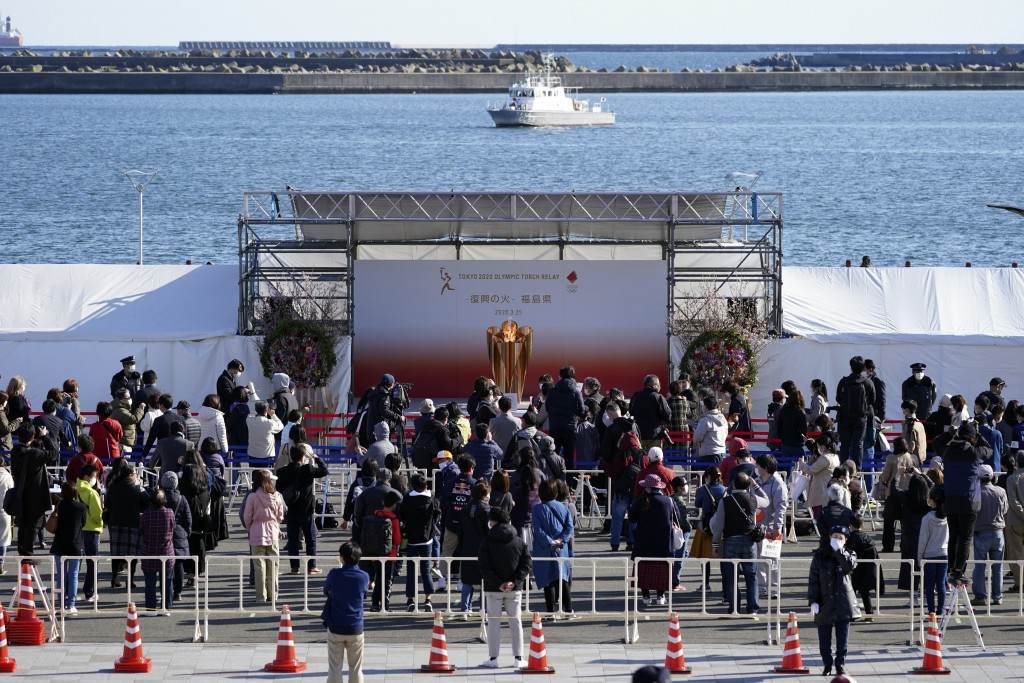 Visitors queue to see the Olympic Flame during a flame display ceremony in Iwaki, Fukushima Prefecture, northern Japan, Wednesday, March 25, 2020. IOC...