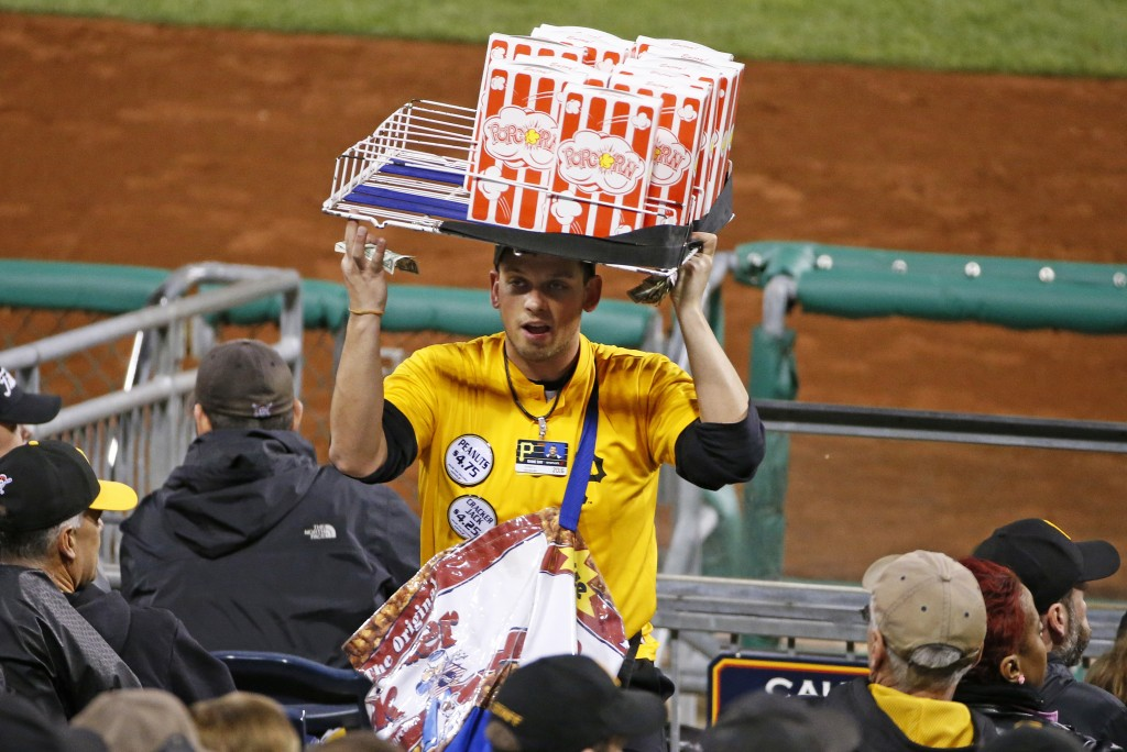 FILE - In this April 29, 2016, file photo, a popcorn and Cracker Jack vendor sells his wares in the stands at PNC Park during a baseball game between ...