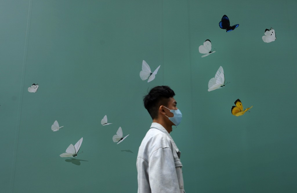 A man wearing face mask walks past a shop at a down town street in Hong Kong Wednesday, March 25, 2020. For most, the coronavirus causes only mild or ...