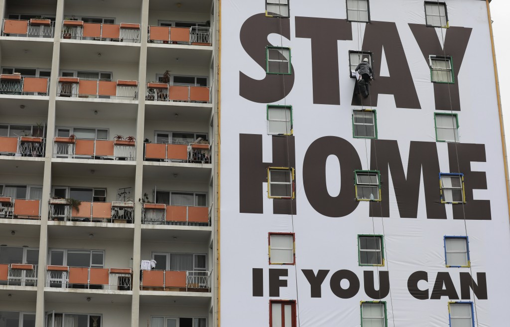 A billboard is installed on an apartment building in Cape Town, South Africa, Wednesday, March 25, 2020, before the country of 57 million people, will...