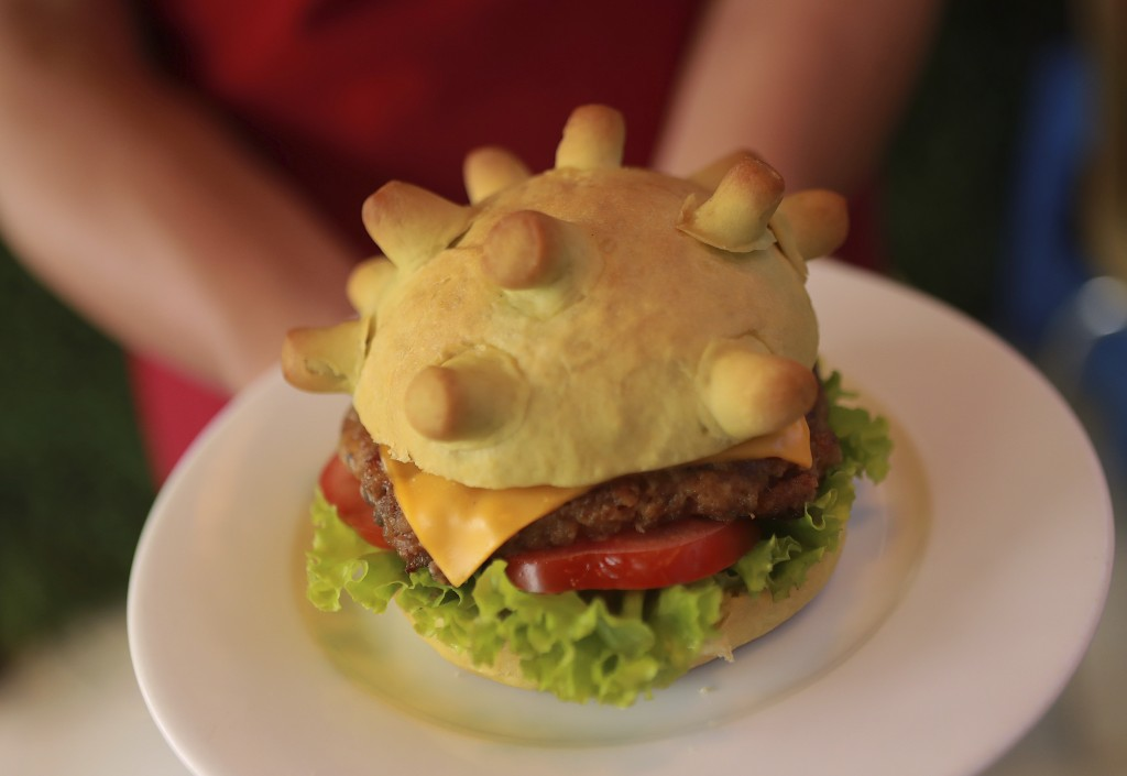 """Restaurant owner Hoang Tung holds up a """"Corona burger"""" in Hanoi, Vietnam on Wednesday, March 25, 2020. As the world is fighting against the Covid-19 p..."""