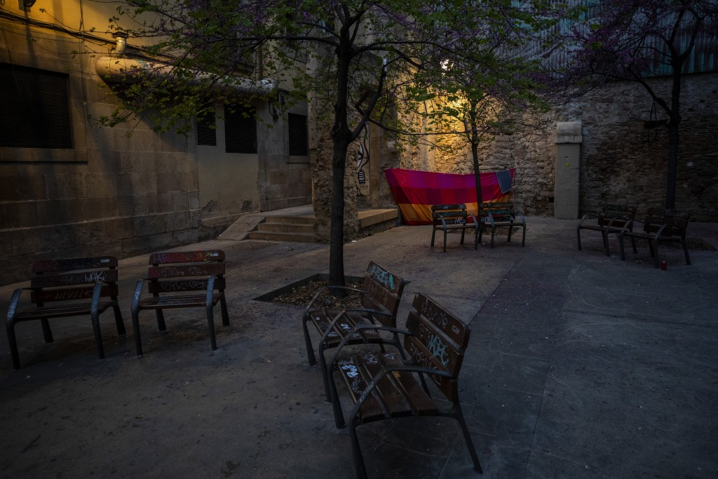 In this Saturday, March 21, 2020 photo, a blanket is used as a shelter in the corner of a square in downtown Barcelona, Spain. With Spain one of the w...