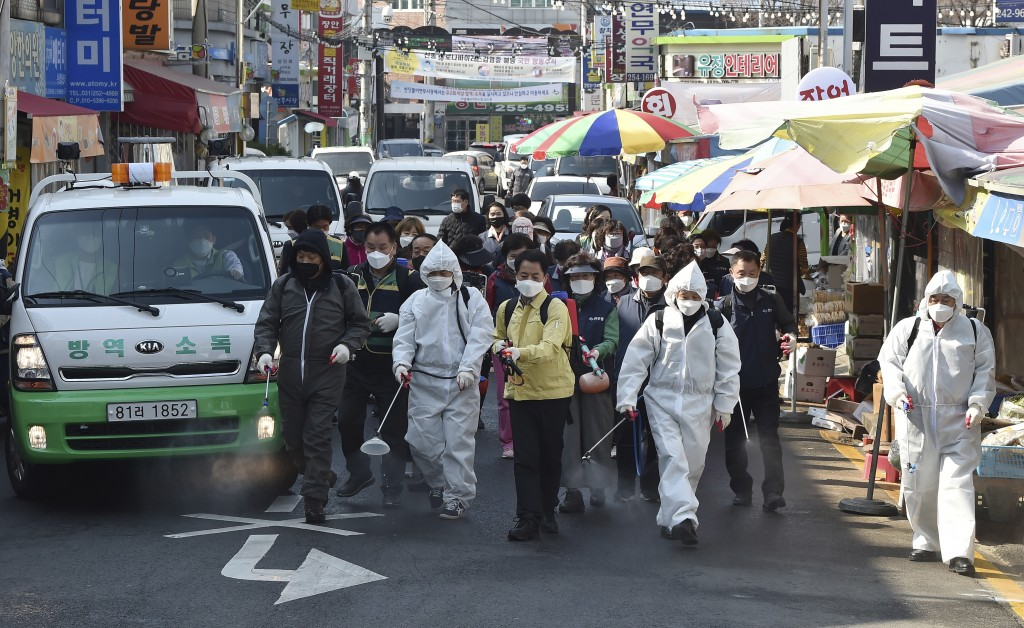 Residents spray disinfectant as a precaution against a new coronavirus at a traditional market in Suwon, South Korea, Wednesday, March 25, 2020. For m...