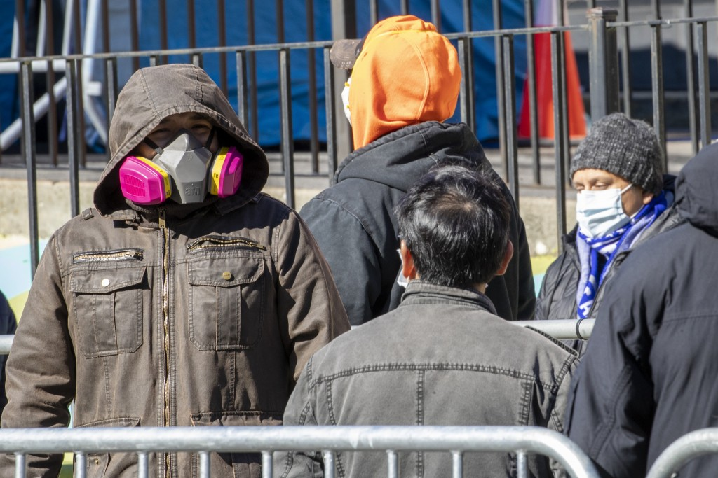 People wear face masks as they line up outside Elmhurst Hospital Center to be tested for the coronavirus, Tuesday, March 24, 2020, in the Queens borou...