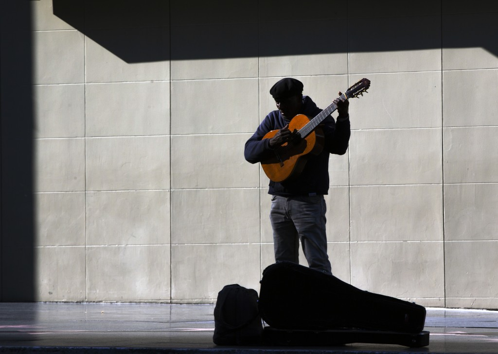 A lone street performer tunes his guitar on the deserted Hollywood Boulevard in Los Angeles on Tuesday, March 24, 2020. A tally by Johns Hopkins Unive...
