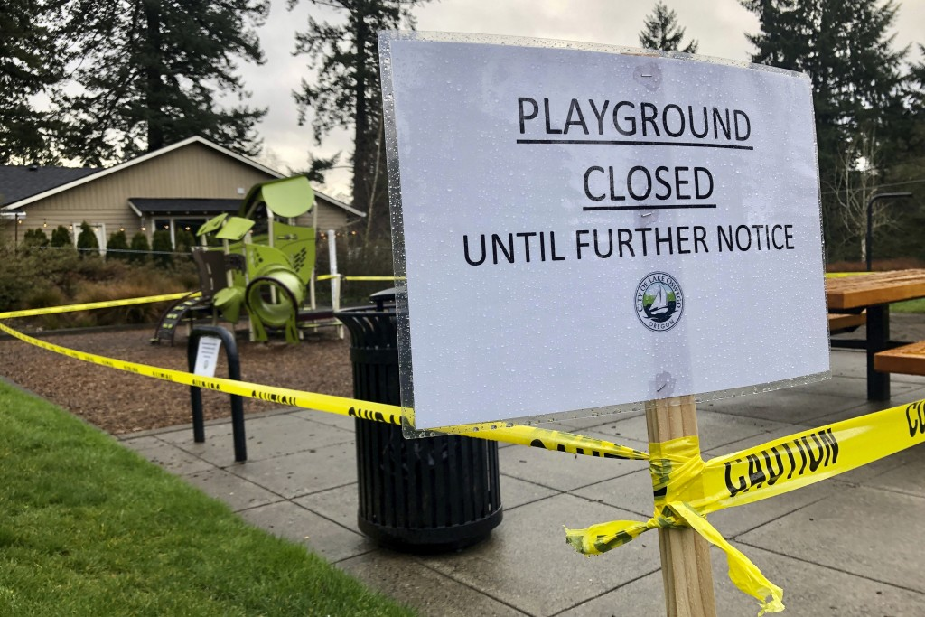 Police caution tape surrounds a playground in Lake Oswego, Ore., on Tuesday, March 24, 2020, the day after Gov. Kate Brown issued a statewide stay-at-...