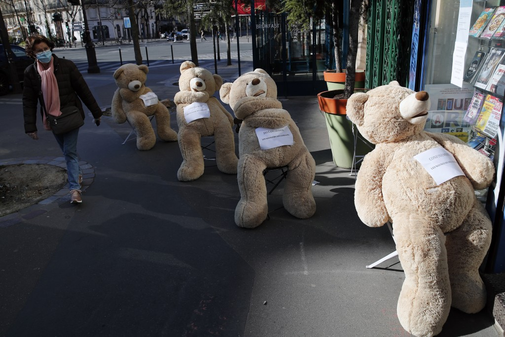 A woman wearing a protective mask walks by a shop with bears installed in line to show social distancing in Paris, Tuesday, March 24, 2020. French Pre...