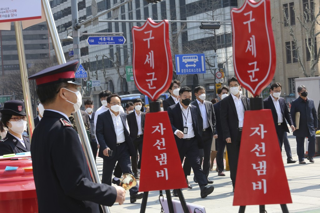 People wearing face masks pass members of the Salvation Army's campaign for the donation of face masks and money to impoverished people amid the sprea...