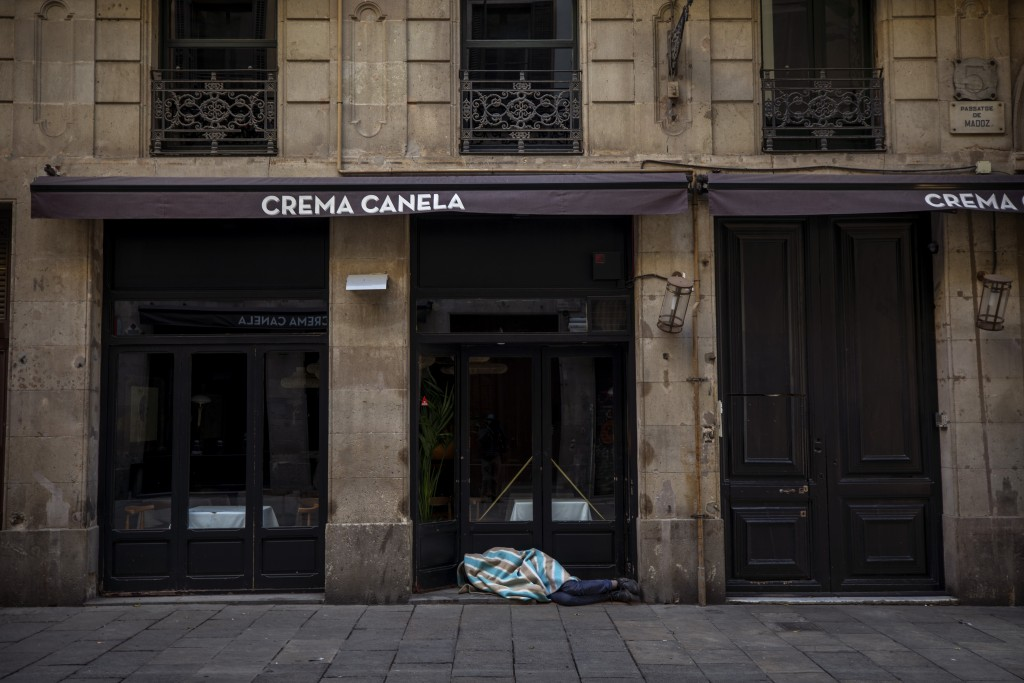 In this Saturday, March 21, 2020 photo, Jose sleeps in the street in downtown Barcelona, Spain. Jose, 27, has been sleeping in the street for 5 years ...