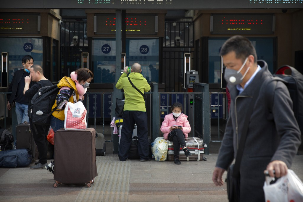 Travelers wearing face masks walk outside the Beijing Railway Station in Beijing, Wednesday, March 25, 2020. Some train stations and bus services reop...