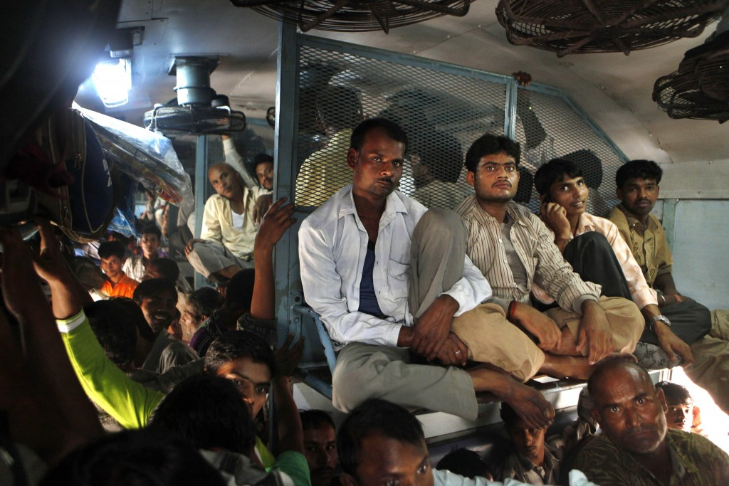 FILE - In this Monday, Oct. 31, 2011, file photo, Indian passengers travel in an overcrowded train at the New Delhi railway station, in New Delhi, Ind...
