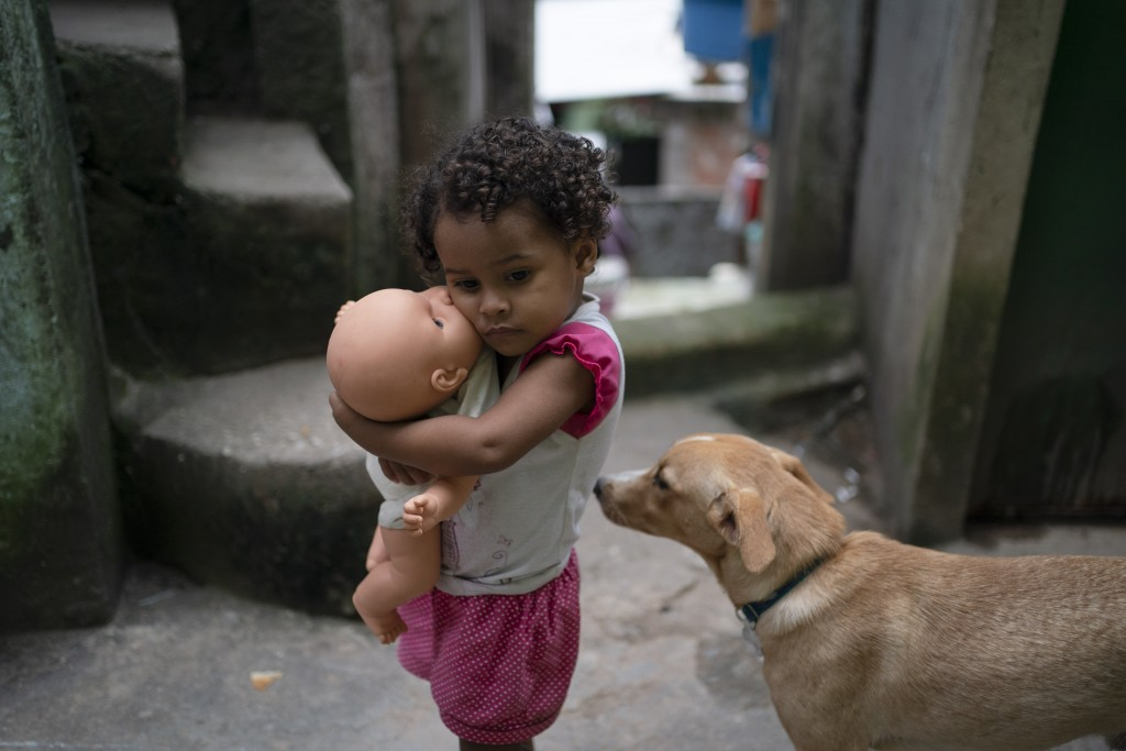 A girl holds her doll in an alley of the Rocinha slum of Rio de Janeiro, Brazil, Tuesday, March 24, 2020. The narrow alleyways of Brazil's largest fav...