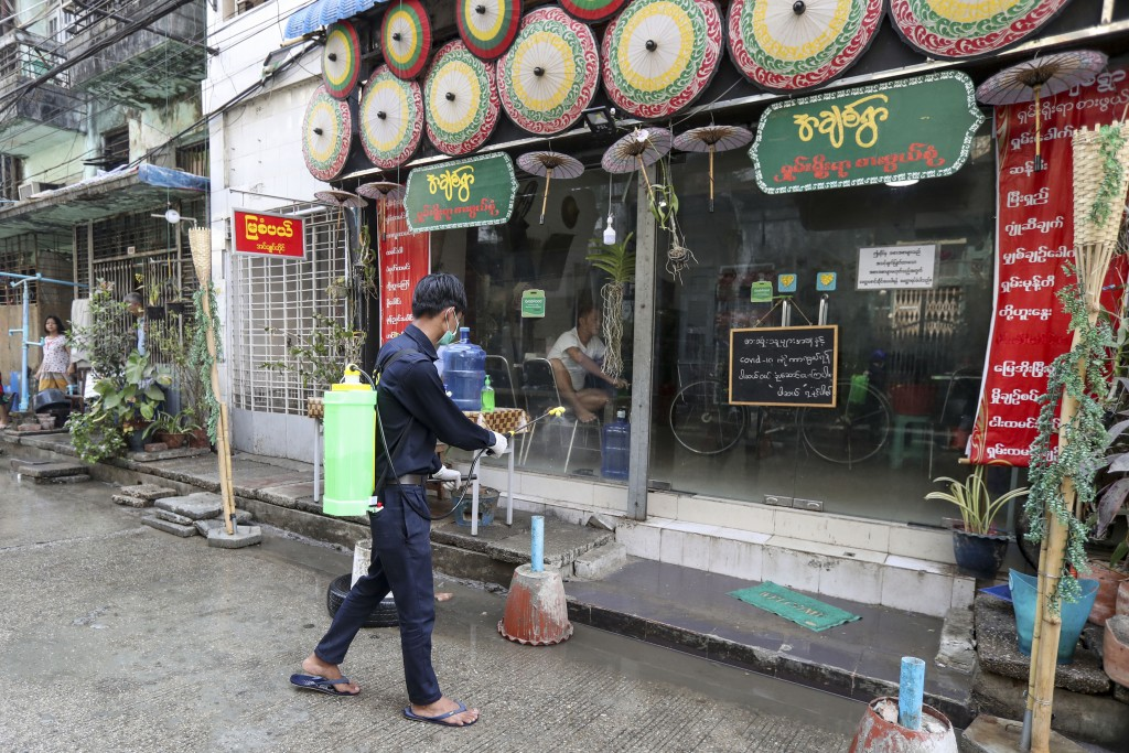 A member of Yangon City and Development Committee sprays disinfectant near a restaurant on a street in hopes of curbing the spread of the new coronavi...