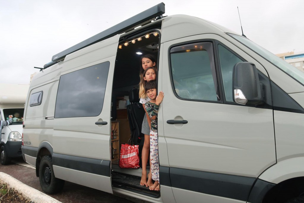 In this photo taken on Tuesday, March 24, 2020, stranded children tourists wait in their motor home as they queue in northern Morocco, near the Spanis...
