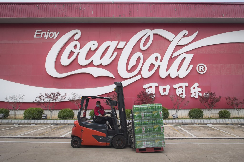 In this Tuesday, March 24, 2020, photo released by China's Xinhua News Agency, a worker wearing a face mask drives a forklift at a Swire Coca-Cola Bev...