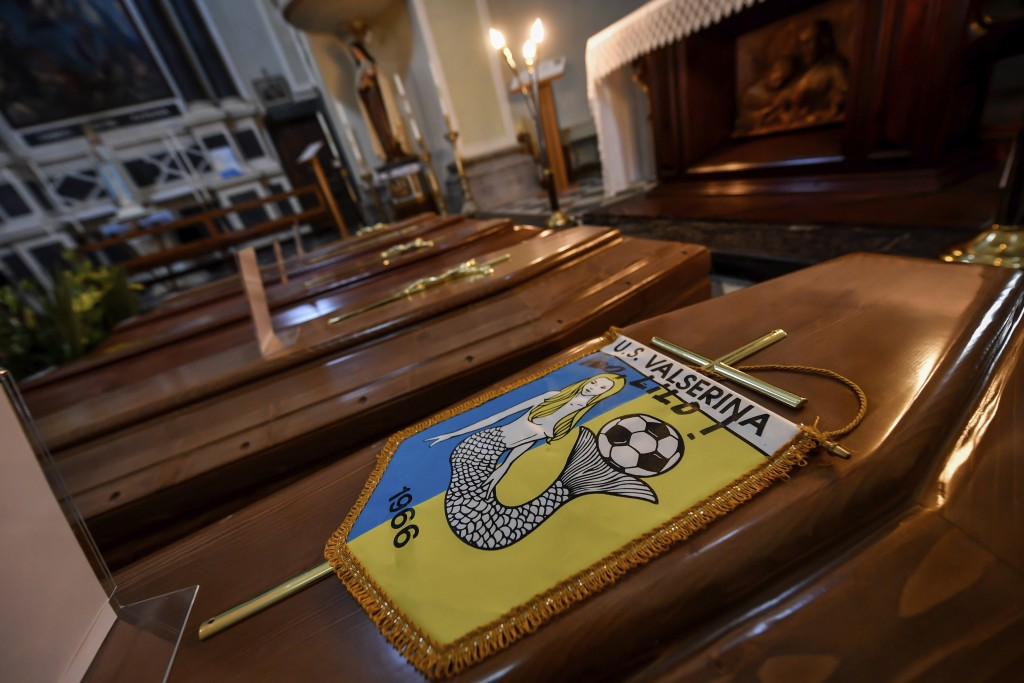 FILE - In this Saturday, March 21, 202 file photo, coffins, one of them with the pennant of the local soccer team, wait to be transported to cemetery,...