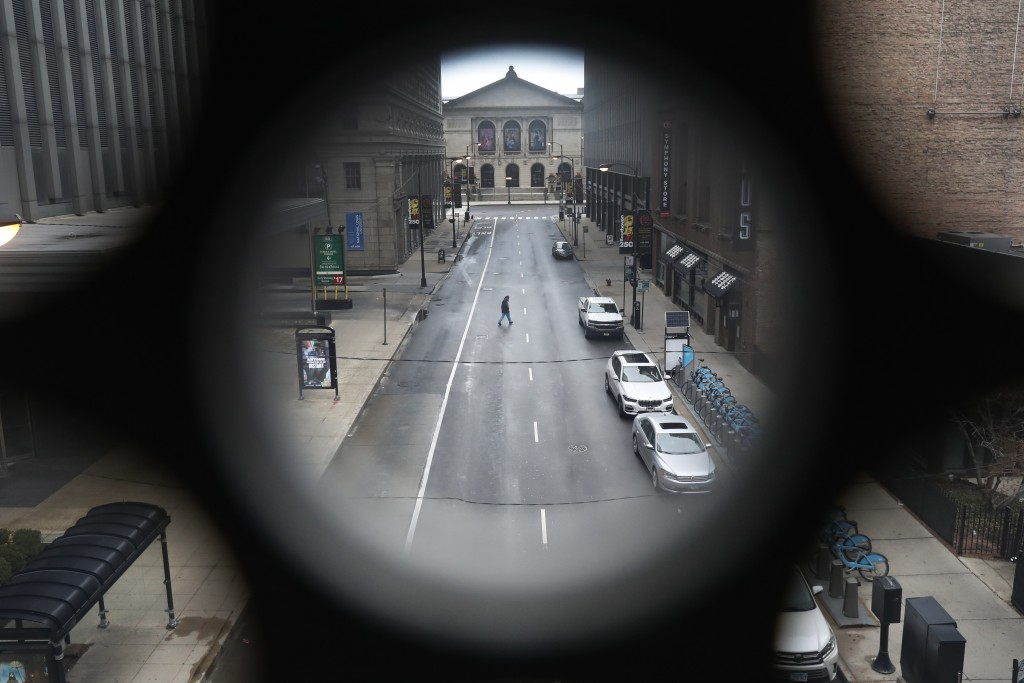 FILE - In this March 23, 2020 file photo, a man walks across a nearly empty Adams Street near The Art Institute of Chicago, in Chicago, on the first w...