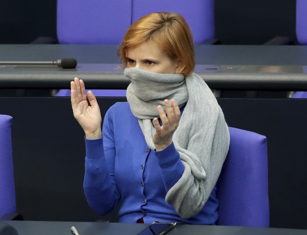 Due to the new coronavirus outbreak Katja Kipping, center, co-chairwoman of the German Left Party, wears a scraf as a face mask during a meeting of th...