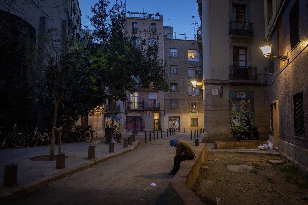 """In this Friday, March 20, 2020 photo, Gana Gutierrez sits in an empty street in Barcelona, Spain. """"It is as if there has been a nuclear explosion and ..."""