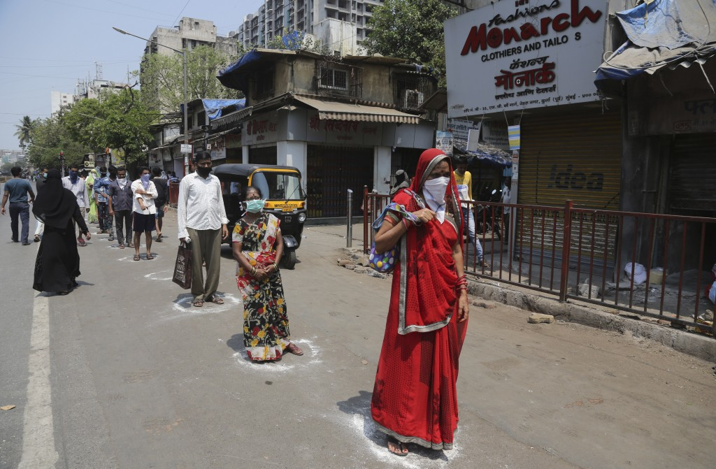 Indians stand in marked positions to buy essential commodities from a grocery store in Mumbai, India, Wednesday, March 25, 2020.The world's largest de...