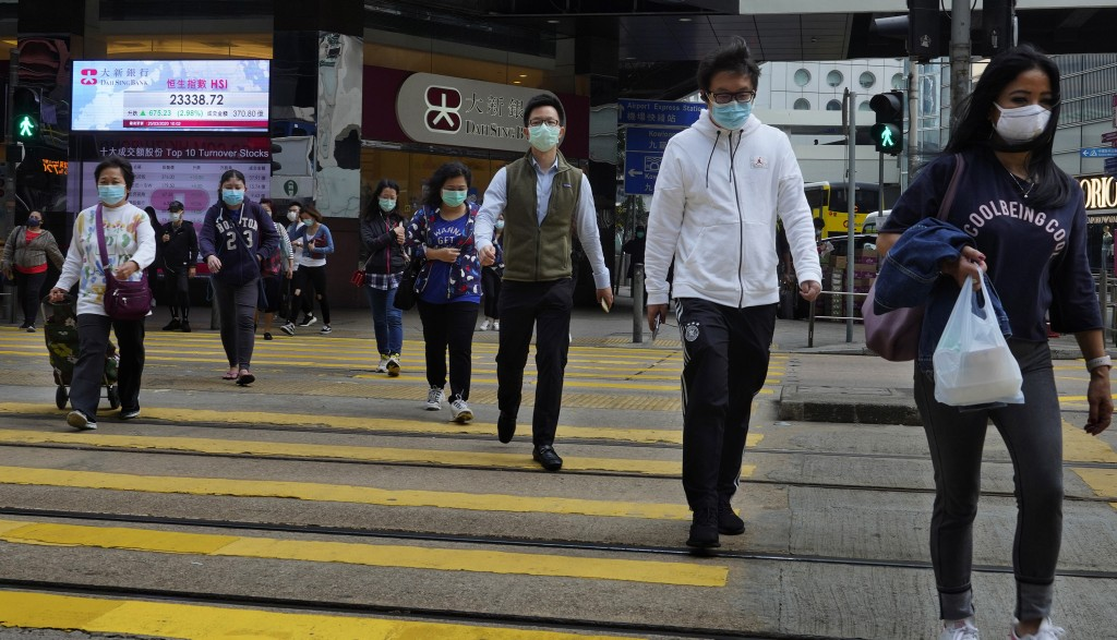 People wearing face masks walk at a down town street in Hong Kong Wednesday, March 25, 2020. For most, the coronavirus causes only mild or moderate sy...