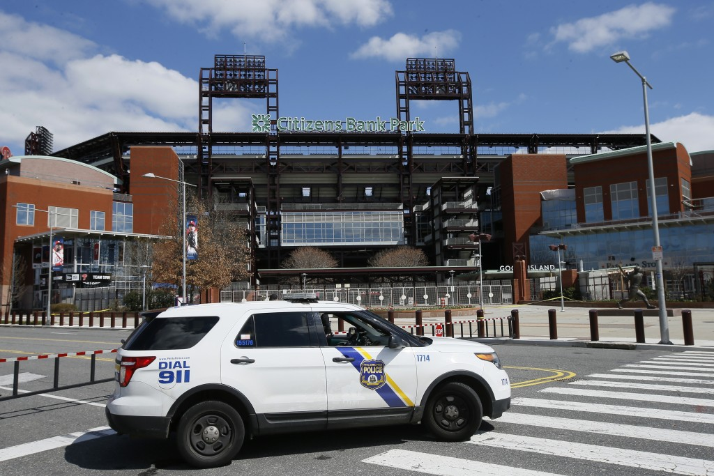 FILE - In this March 24, 2020, file photo, a Police vehicle blocks a street near Citizens Bank Park, home of the Philadelphia Phillies baseball team, ...
