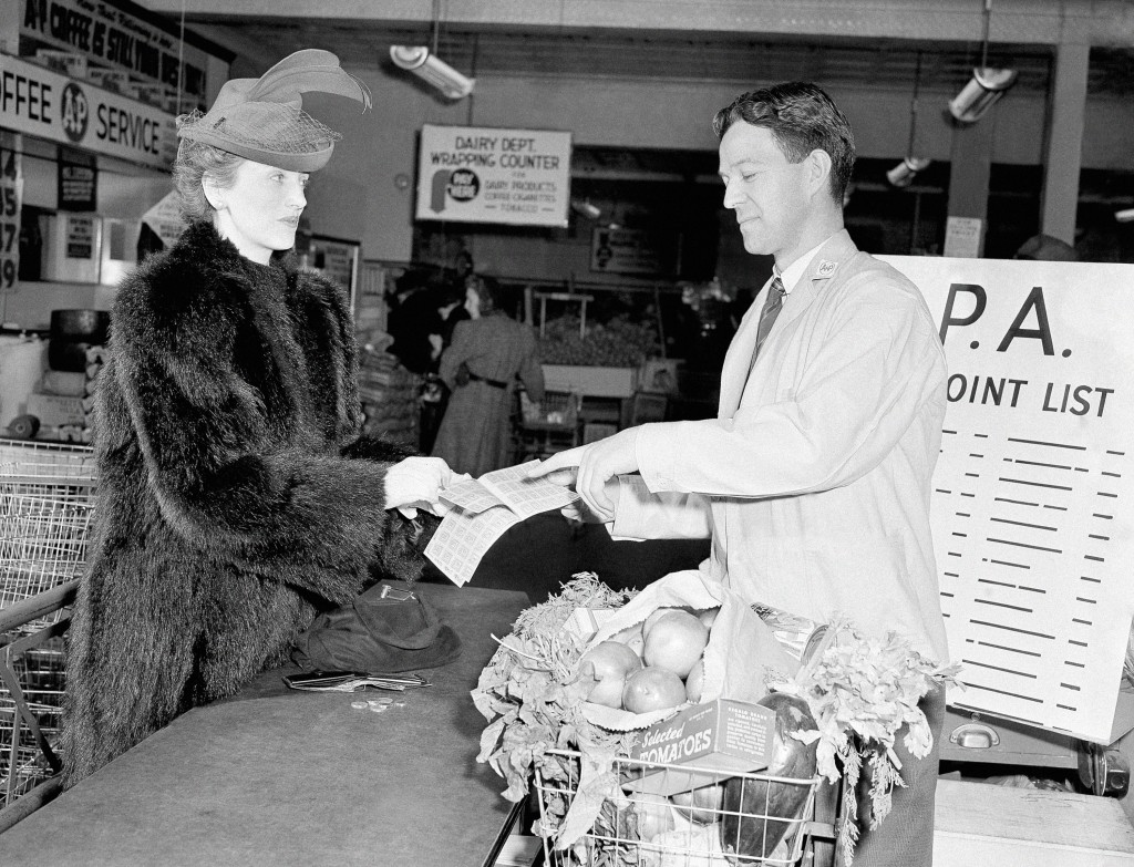 FILE - In this Feb. 14, 1943 file photo Mrs. Caven holds her new point ration book as the grocer indicates the proper stamps to cover purchases in New...