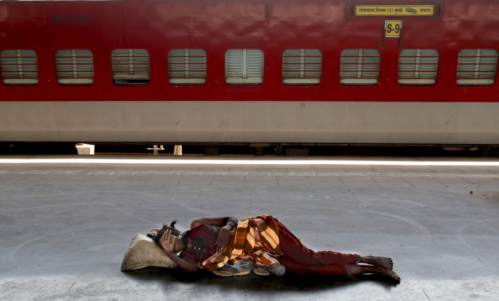 FILE - In this Monday, March 23, 2020, file photo, a homeless woman sleeps on a deserted platform of Lokmanya Tilak train terminus in Mumbai, India. I...