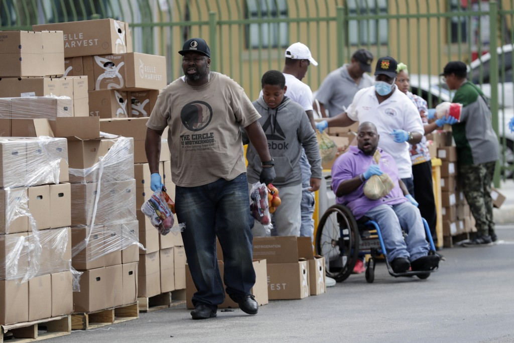 Sinclair Manley, a volunteer with the Circle of Brotherhood, left, passes out fresh fruit to local residents impacted by the new coronavirus at a food...